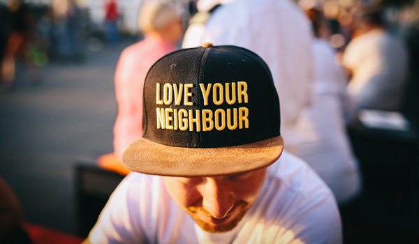 close up of a man's hat with the words love your neighbor
